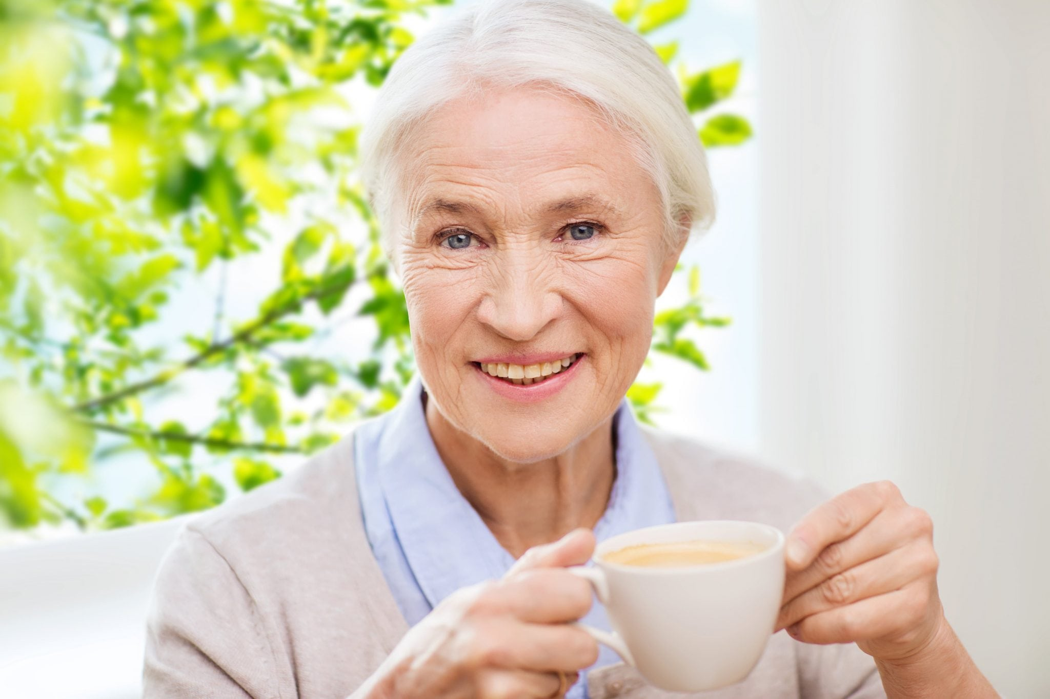 age, drink and people concept - happy smiling senior woman with cup of coffee at home over window and green natural background