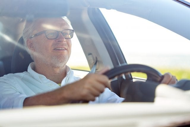 road trip, travel and old people concept - happy senior man in glasses driving car