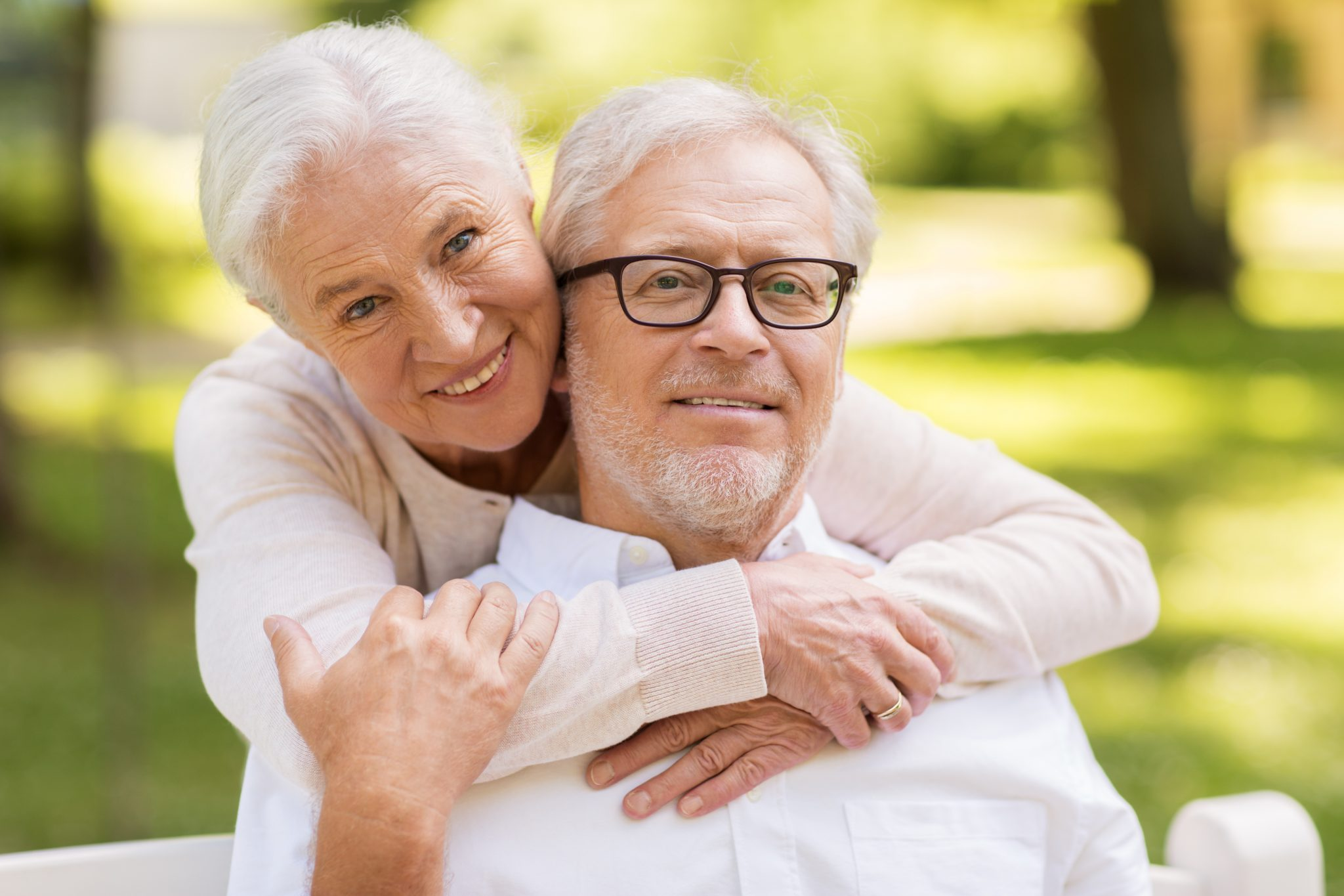 old age, relationship and people concept - portrait of happy senior couple hugging at summer park